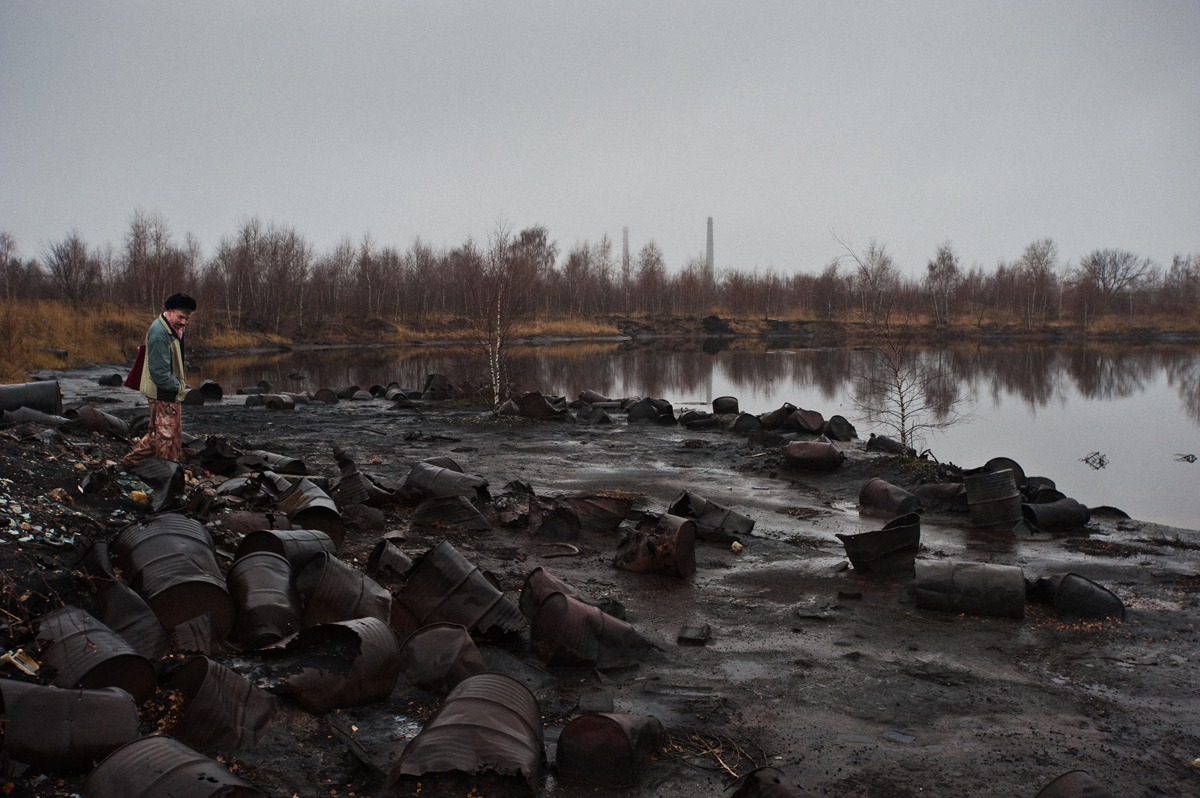 DZERZHINSK, RUSSIA-DECEMBER 2009:  Dmitry Levashov  stands  near the oily stinking lake filled with thick black and red chemical waste which lies in a  field of dead trees . There are about 50 landfills brimming with industrial and chemical waste in the town. Primarily the waste contaminates the subterranean water, which is used by people living in villages nearby. For example, in a reservoir situated 50 meters down from the Beloe More (White Sea) factory, the water is salty because the chlorogenic compounds have been leaking into it from the concrete dump for the last 30 years.